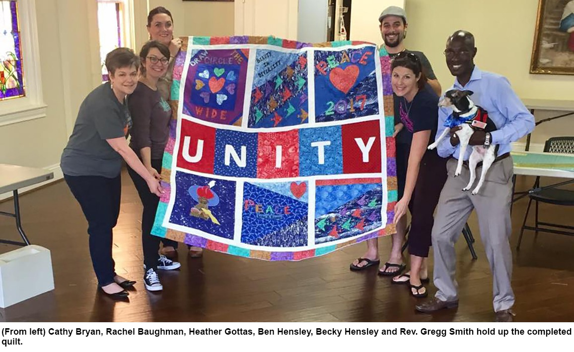 From left: Cathy Bryan, Rachel Baughman, Heather Gottas, Ben Hensley, Becky Hensley, and Rev. Gregg Smith hold up the completed quilt.