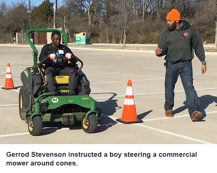 Gerrod Stevenson instructs a boy on a mower