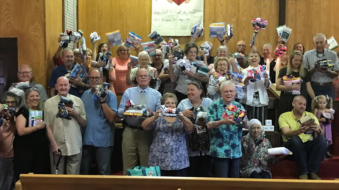 Church members hold up their donations
